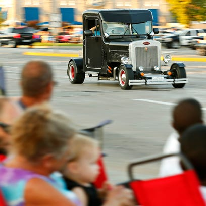 A vintage car drives past onlookers near the intersection