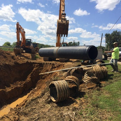 Crews work on a drainage pipe project in Richmond Dale