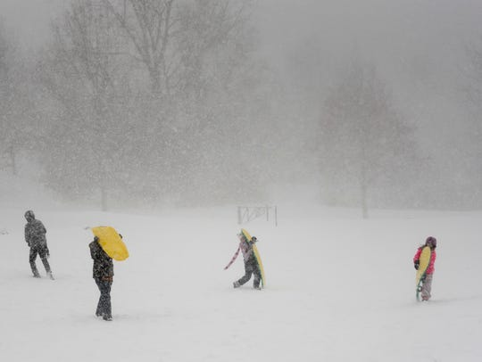 Sledders make their way through a snow squall at Heritage