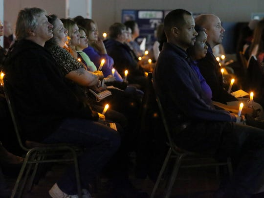 Attendees watch a video tribute to victims during the