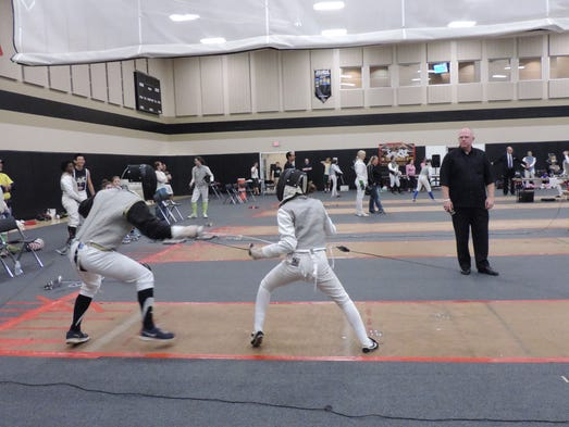 Team members and coach watch as fencers duel at 2014