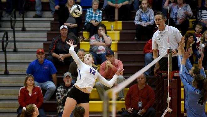 Highland sophomore Raina Terry goes high to hit the ball Saturday afternoon during a Division II district championship volleyball match against Granville, which won 3-2.