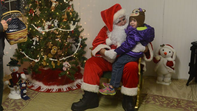 Alayna Burr, 4, visits with Santa as he makes a stop in downtown Fremont during the Once Upon a Christmas on Friday, Dec 5, 2014.