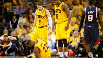 LeBron James of the Cleveland Cavaliers gets up from the court as Matthew Dellavedova and Tristan Thompson look on in the third quarter against the Atlanta Hawks during Game Three of the Eastern Conference Finals of the 2015 NBA Playoffs at Quicken Loans Arena.