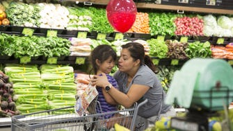 Leonela Rodas kisses her four year old daughter Ruth while they shop during the grand opening of the Sprouts Farmers Market in Mesa, Az.