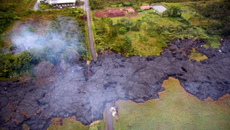Lava flows over Cemetery Road and Apa'a Street near the town of Pahoa on the Big Island of Hawaii on Oct. 29, 2014.