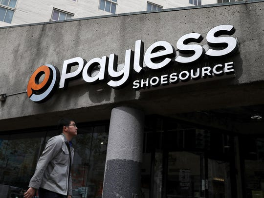 A pedestrian walks by a Payless Shoe Source store on