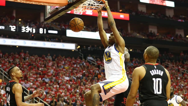 Golden State Warriors forward Kevon Looney (5) dunks against Houston Rockets guard Gerald Green (14) and guard Eric Gordon (10) during the third quarter in game one of the Western conference finals of the 2018 NBA Playoffs at Toyota Center.