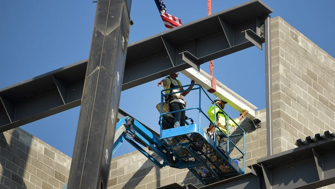 WORCESTER - Construction workers place the final beam Wednesday, Oct. 7, 2020, atop the Veterans Administration community-based outpatient clinic being built at 403 Belmont St. on the UMass Medical School campus.
