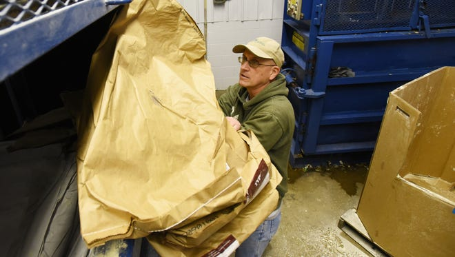 Don Mount loads bags into a baler at Goodwill Industries recently.