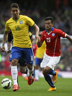 Brazil's Roberto Firmino challenges for the ball with Chile's Roberto Gutierrez during the international friendly soccer match between Brazil and Chile.