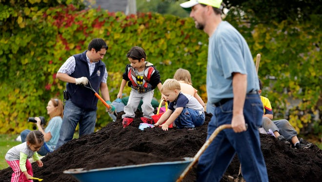 Large and small helpers work on a community garden at St. Therese Catholic Parish in Appleton on Oct. 12, 2013.