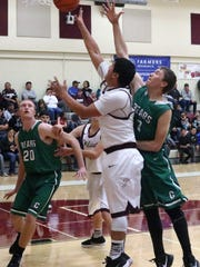 Tularosa's Toby Carrillo takes a shot at the basket while being guarded by Cloudcroft's Marshall Virden.