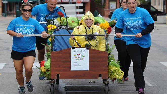 """In this 2014 photo, the Monroe County Department of Human Services """"Bed Bug"""" team consisted of Julie McLaughlin, Tim Kelly, Amanda Masserant, Maribel Alvarado and riding Randi Sheldon in the Bed Race to Aid Children in downtown Monroe."""