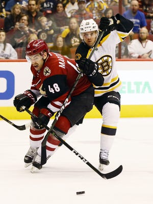 Arizona Coyotes' Jordan Martinook is slowed down in front of the goal by Boston Bruins' David Krejci in the 2nd period on Saturday, Nov. 12, 2016 in Glendale, Ariz.