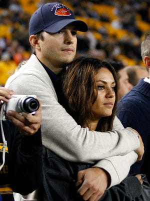 Ashton Kutcher and Mila Kunis look on from the sidelines before the game between the Chicago Bears and the Pittsburgh Steelers on Sept. 22, 2013 at Heinz Field in Pittsburgh.