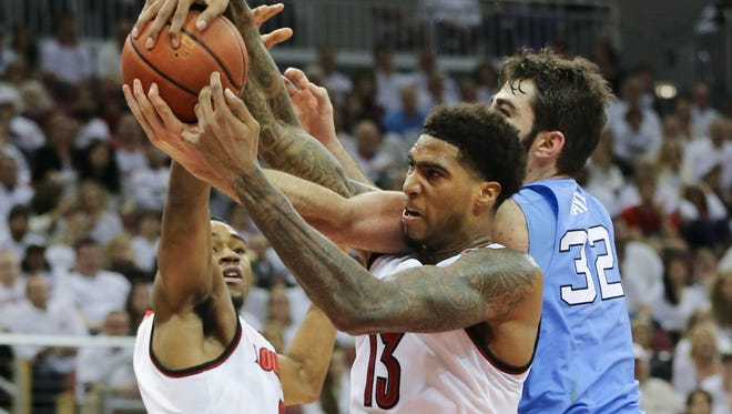 U of L's Ray Spalding (13) and V.J. King (0) worked against North Carolina's Luke Maye (32) during their game at the Yum Center.    