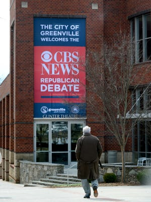 A person walks past a poster advertising the CBS News Republican Debate at the Peace Center on Monday, February 8, 2016.