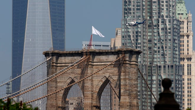 An NYPD helicopter flies over the Brooklyn Bridge inspecting white flags that replaced American flags sometime overnight on Tuesday.