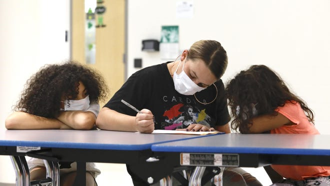 Nikole Cabrera, center, registers her daughters Amaya English, left, 9, for fourth grade and Imariana Williams, 8, for third grade on Wednesday at Constance Lane Elementary School in Rockford.