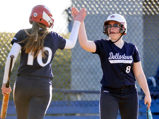 Dallastown's Amanda Jones, left, and Kayla Collins high-five after Jones scored the eventual winning run on Jenna Eckenrode's single vs. Red Lion on Friday. The Wildcats won, 7-6. (Daily Record/Sunday News -- Chris Dunn)