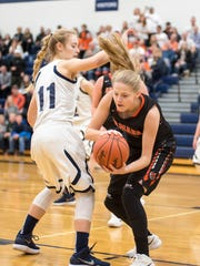 Marysville's Gabby Fogarty (11) and Armada's Harper Nebergall fight for a rebound during the MHSAA Class B district finals at Marysville High School March 2.
