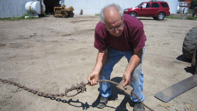 George Drontle shows where the chain was attached to the cable. The chain was adjusted as the stump gave way.