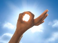 Man's hand in front of the sun