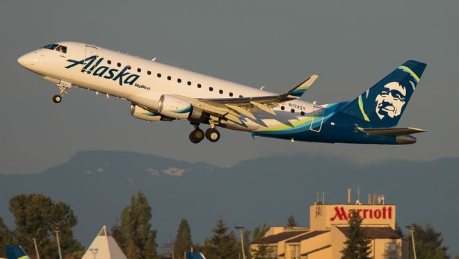 An Alaska Airlines Embraer E170 takes off over company metal at Seattle Tacoma International Airport in May 2017.