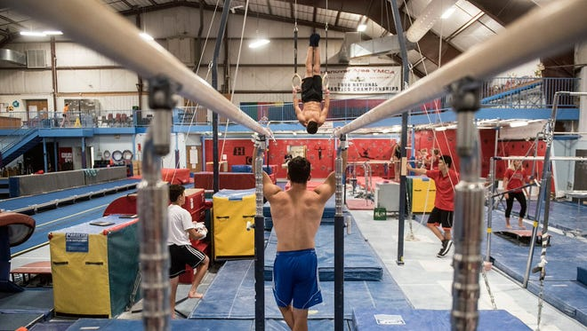Gymnast Jacob Cooke watches a teammate perform a routine on the rings during practice at the Hanover YMCA.