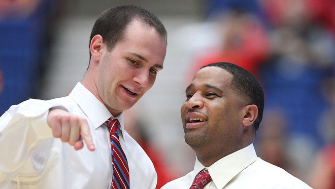 """Arizona graduate assistant coach David Miller, left, and assistant coach Emanuel """"Book"""" Richardson share a laugh before the No. 1 University of Arizona Wildcats vs. Arizona State University men's college basketball game on Thursday, Jan. 16, 2014, at McKale Center in Tucson, Ariz."""