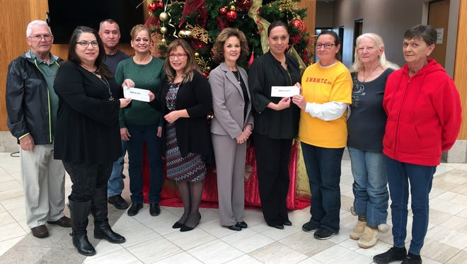 1st New Mexico Bank handed out its annual holiday awards to benefit local organizations in the community. This year's recipients of the monetary checks were the Deming-Luna County Commission on Aging and the Southwest New Mexico Transition Center. The COA operates the Deming Senior Citizen's Center on a tight budget and the SWNMTC is a program that helps veterans. Pictured, from left, are: John Pace, Julie Bolton, Danny Cordova, Maria Hernandez, Rosa Perez, Teresa Molina, Roxana Rincon, Cabrini Martinez, Anna Tobin and Pat Johnson.