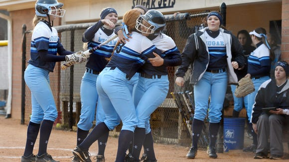 Enka's Mariah Foxworth hugs Whitney Fletcher, right, after one of her two home runs on Friday in Candler.