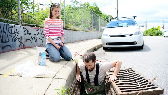 Anna Alsobrook, MountainTrue watershed outreach coordinator, watches as Hartwell Carson, MountainTrue French Broad Riverkeeper, lowers himself into a storm drain on Roberts Street in the River Arts District to collect a water sample on Thursday, May 25, 2017.