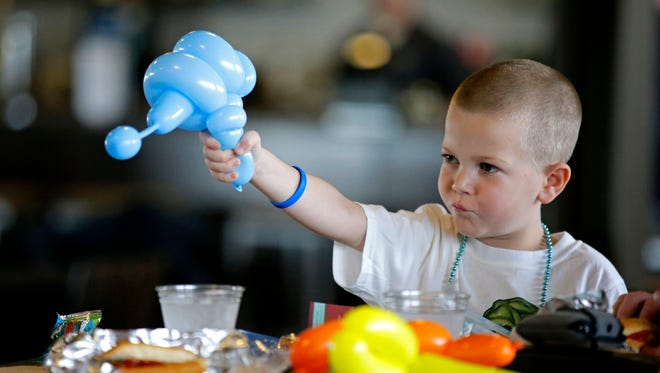 Beckett Roerdink plays with a balloon during a birthday fundraiser for him at Fox Cities Stadium on Sunday.