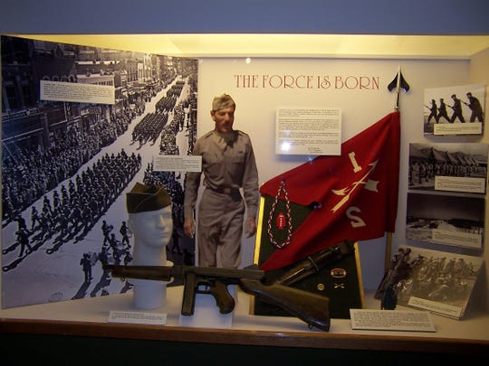 The Force is Born display at the Montana Military Museum. Pictured on the left is the Force's parade on April 6, 1943, in Helena, Montana. Col. Frederick is pictured in the middle above the Thompson M1A1 submachine gun and a V-42 stiletto knife below the flag.