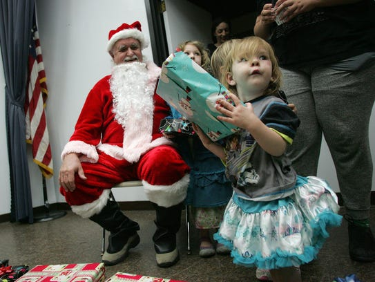 Celeste McGarry, 2, carries her Christmas present given
