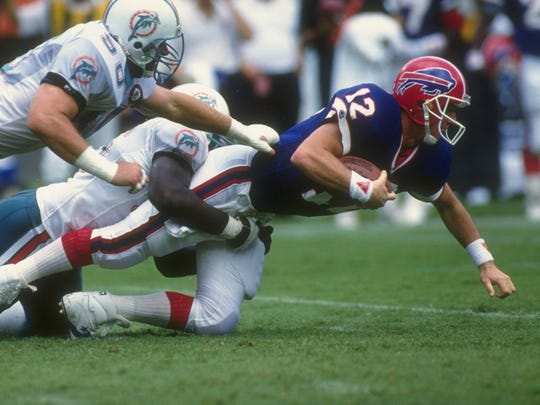 Quarterback Jim Kelly of the Buffalo Bills (right) gets tackled by a pair of Miami Dolphins players.