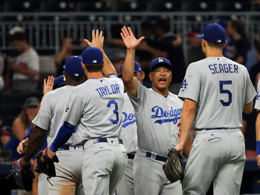 Los Angeles Dodgers manager Dave Roberts (30),center, celebrates with his players after defeating the Atlanta Braves in a baseball game Tuesday, Aug. 1, 2017, in Atlanta. The Dodgers won 3-2. (AP Photo/John Bazemore)