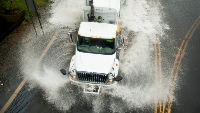 A truck driver navigates through a flooded portion of the Brooklawn Circle as heavy rain falls on Wednesday afternoon.  04.30.14