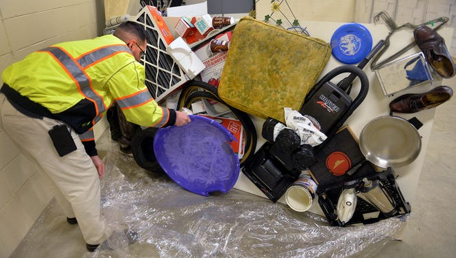 St. Cloud Public Works Maintenance Supervisor Dan Legatt on Dec. 16 shows a display of items collected during just one week that were placed in recycling bins in error. The city hopes to educate residents to keep items that can't be recycled out of the recycling stream. Pizza boxes and drink cups, a vacuum, coffee pots, irons, shoes, toasters, and couch cushions were found.