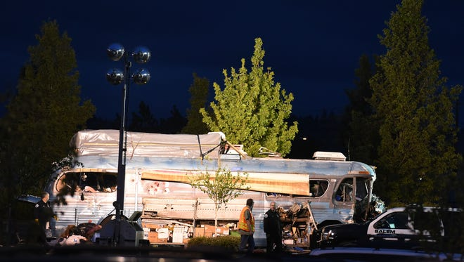 Police investigate the scene of a shootout and standoff on Friday, in the parking lot of Walmart along Turner Road in Salem.