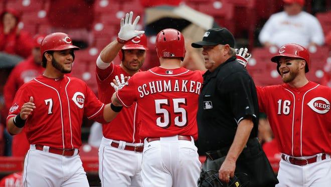Cincinnati Reds' Skip Schumaker (55) celebrates his three-run home run off St. Louis Cardinals starting pitcher Lance Lynn with Eugenio Suarez (7), Joey Votto, center left, and Tucker Barnhart (16) in the fifth inning.