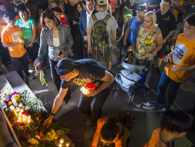 Mourners lay flowers and candles for victims of the