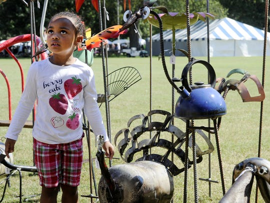 Erynn McCondichie, of Nashville, looks over some of the yard and garden creations during a previous TACA Fall Craft Fair at Centennial Park.