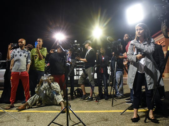 Reporters and onlookers gather for a press conference in the parking lot of Crossroads Center early in the morning following the Sept. 17 attacks at the mall.