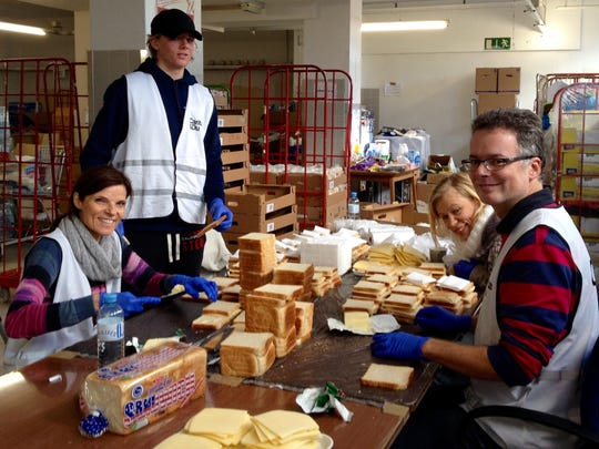 Volunteers with Caritas, a Catholic service organization, making sandwiches for refugees at the nearby train station in Salzburg, Austria.