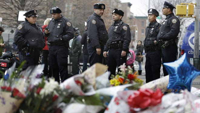 New York City police officers gather near a makeshift memorial near the site where fellow officers Rafael Ramos and Wenjian Liu were murdered in Brooklyn.