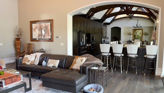 The design of a large open-concept living room, kitchen and dining room at this Marion Township home located on a 200-acre game ranch was inspired by wife Judi DeKroub's love of European architecture and world travel.