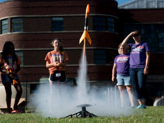 """Becca Campbell of Boonville, Ind., second left, fires her rocket after a countdown of """"3... 2... 1... blast-off"""" at the University of Evansville's Engineering Options for Girls camp for middle school girls Wednesday morning."""